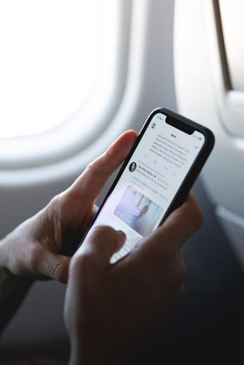 person's hands holding a smartphone next to an airplane window