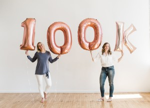 two women celebrating 100k in sales with 100k balloons