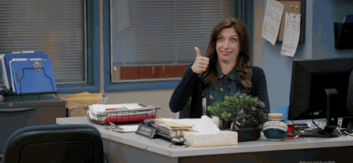 woman giving thumbs up sitting at a desk