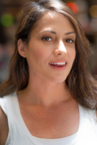 headshot of a woman with brown hair wearing a white tank top