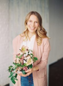 headshot of a woman holding a bouquet of flowers